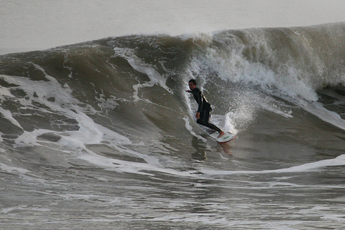 An unknown surfer cruises along a clean face at East Runton, Norfolk