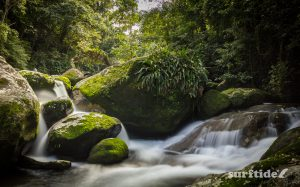 Long exposure photo of water cascading over moss-covered rocks at Cachoeira da Laje, Ilhabela in Brazil