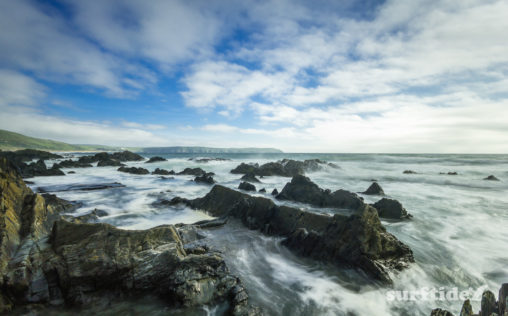 Long exposure photo of the waves breaking on the rocks next to Barricane Beach in North Devon, England
