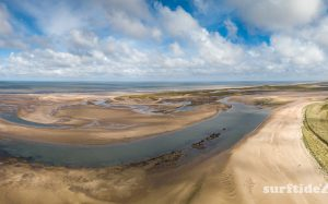 Aerial photo of Brancaster beach at low tide showing the vast expanse of sand and water draining back into the sea