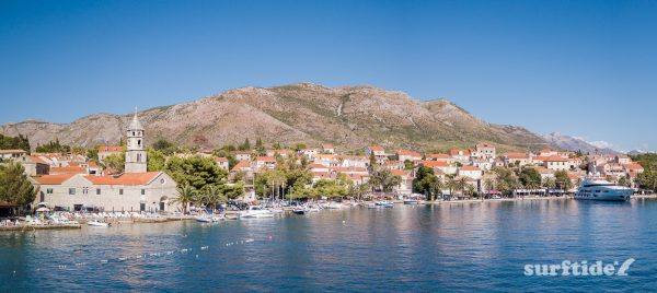 Panoramic photo showing the historic architecture, blue sea and boats in Cavtat harbour in southern Croatia