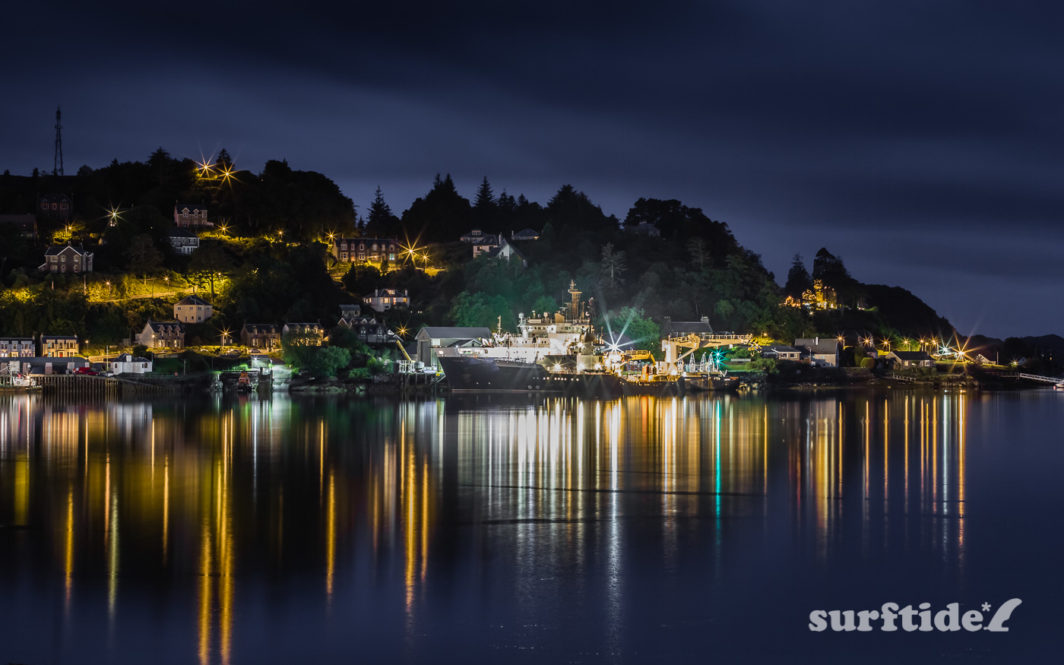 Long exposure night photo of boats and light reflecting off the water in Oban harbour, Scotland