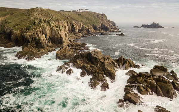 Aerial photo of the waves crashing in on the rocks at Land's End, Cornwall, England