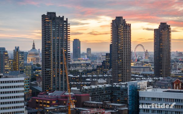 High dynamic range photo of the Barbican Towers at sunset with the London skyline as a backdrop