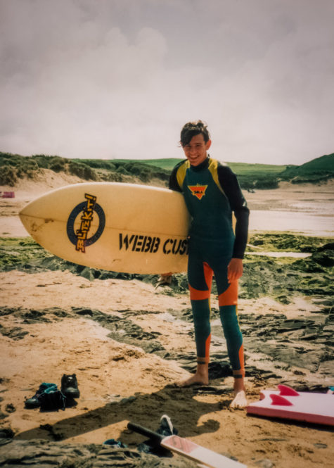 Ben holding his first surfboard on a family trip to Looe in Cornwall, 1993.