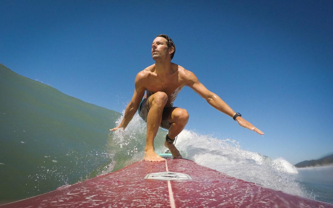 Ben Ellis surfing a wave on a longboard at Praia da Lagoinha, Ubatuba, Brazil in 2018