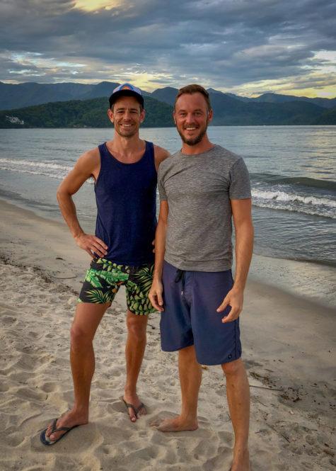 Ben Ellis & Simon Price standing on the sand, Praia do Itaguá, Ubatuba, Brazil in 2018