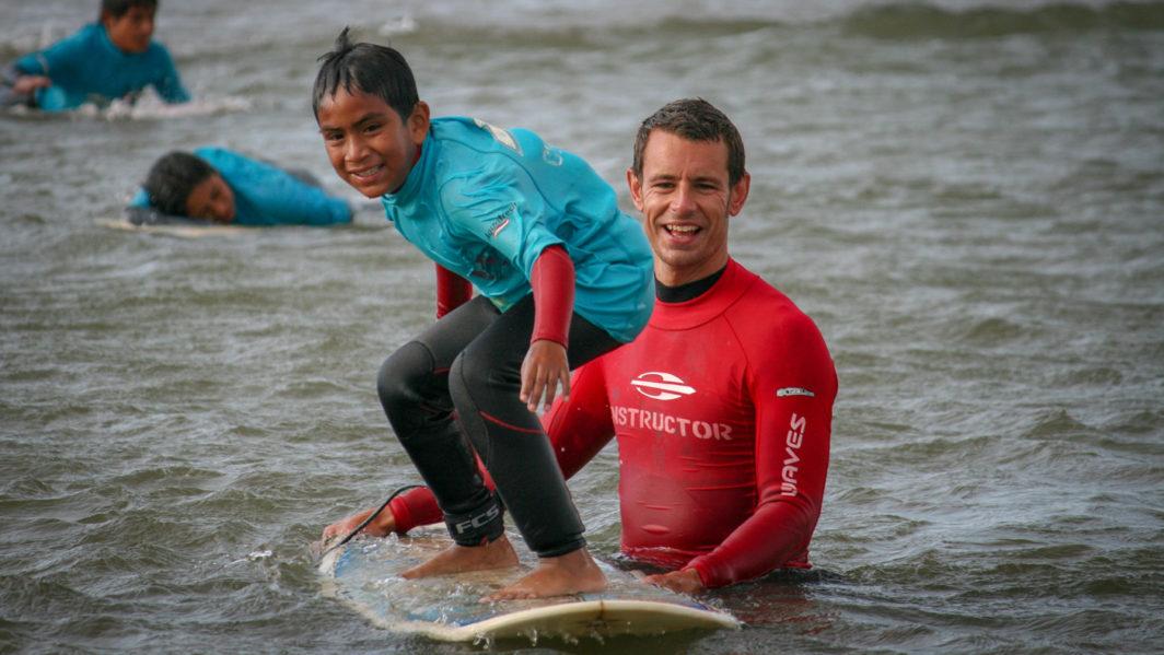 Ben Ellis teaching children to surf for WAVES For Development, Lobitos, Peru in 2010