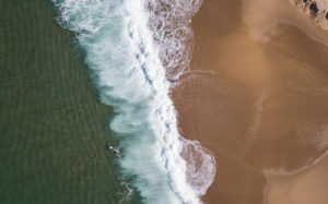An aerial shot of a surfer paddling out to catch waves
